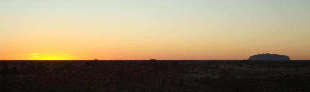 Panoramic of sun set with Uluru to the side