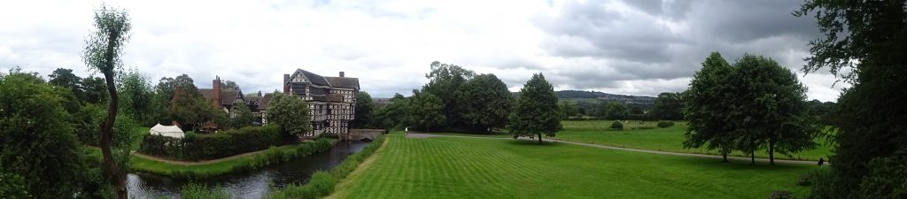 Panoramic Of Little Moreton Hall With Mow Cop In The Distance