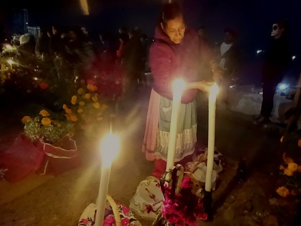 Mexican Lighting Candles On Altar In Graveyard For Day Of The Dead