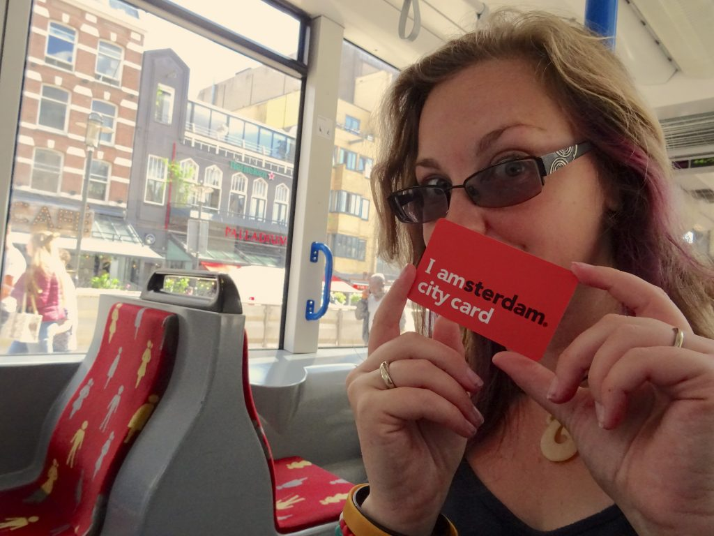natpacker holding i Amsterdam City Card On Tram