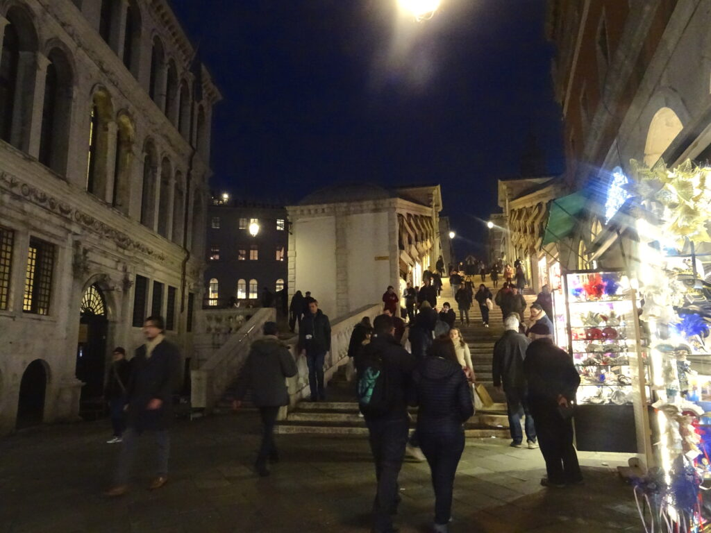 Ramp Leading Up Rialto Bridge At Night With Shops And People Walking