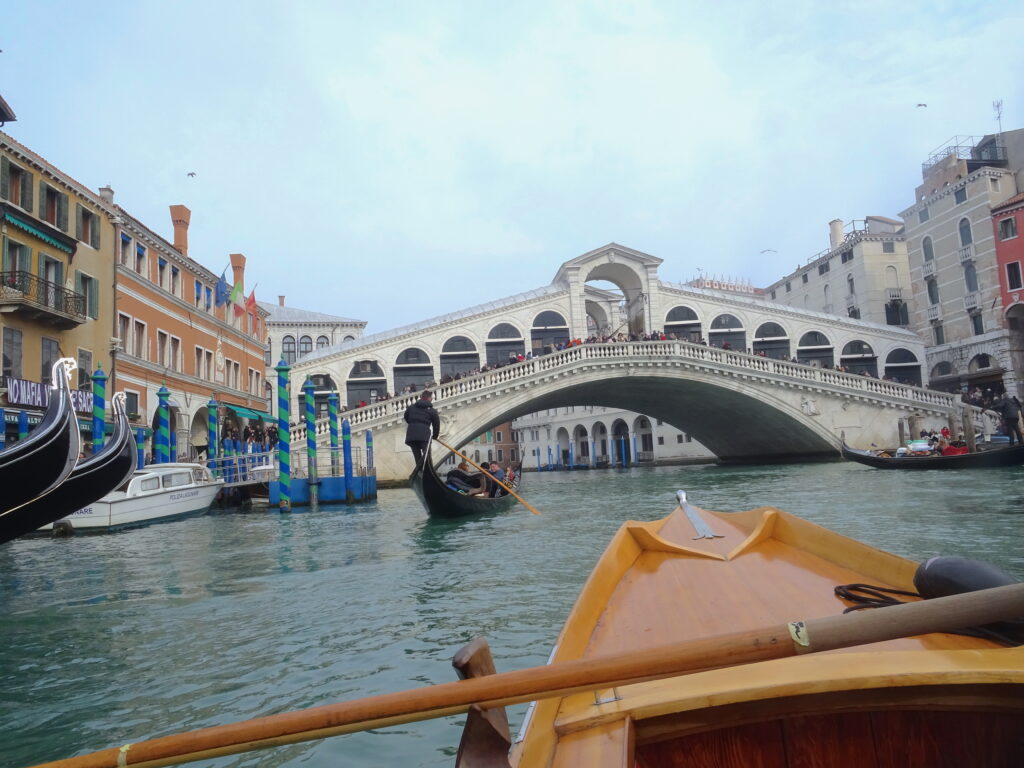 Approaching Rialto Bridge By Water With A Gondola In Front