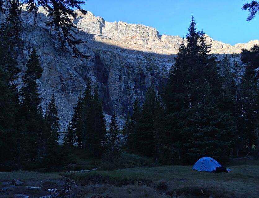 Camping tent in the shadow of mountains