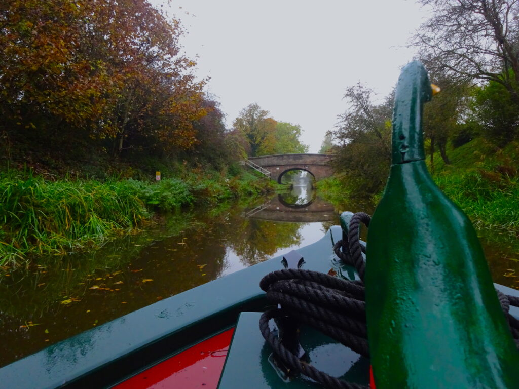 View Of Canal With Bridge And Reflection From The Front Of A Narrowboat