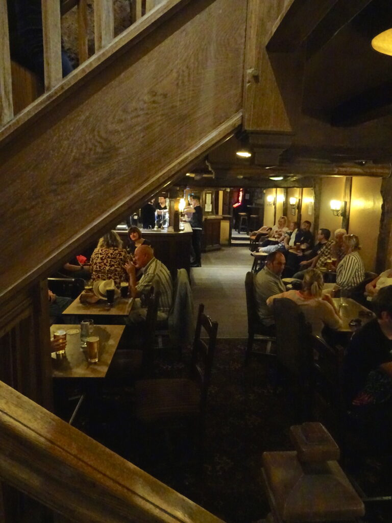 Looking Down On The Interior Of A Dark Pub From The Stairs