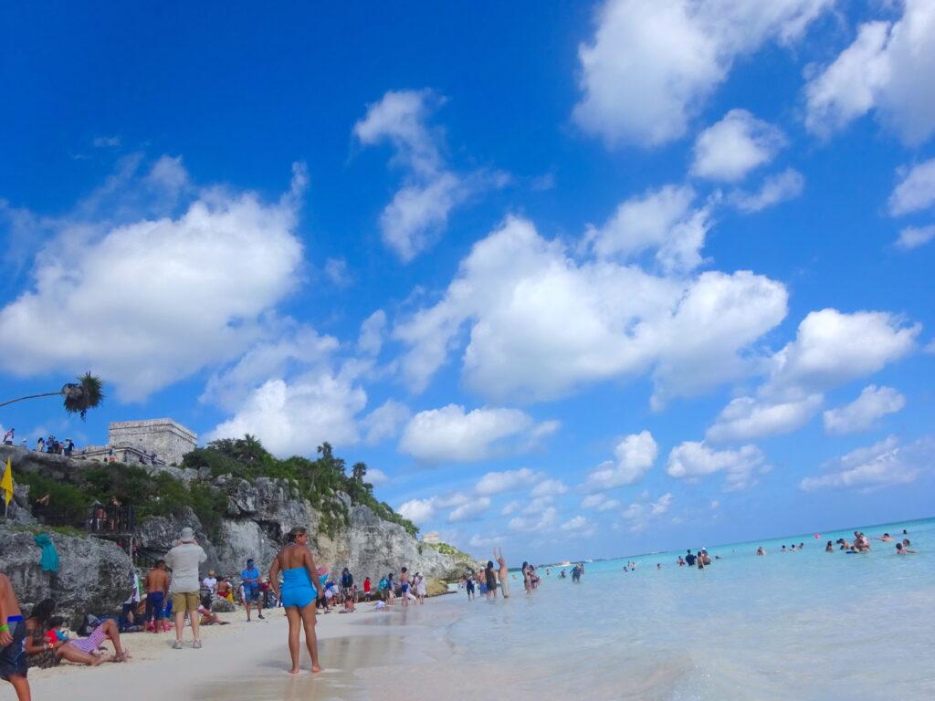 Tourists On The Beach Under Tulum Ruins