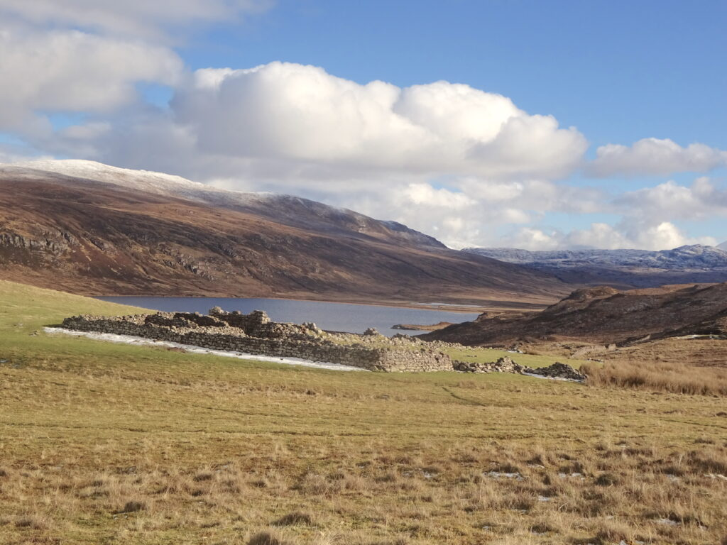Ruins And A Loch With Hills In The Distance